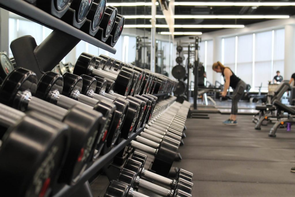 picture of empty gym with woman avoid working out